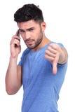 Junger zufälliger Mann mit schlechten Nachrichten am Telefon Stockfotografie