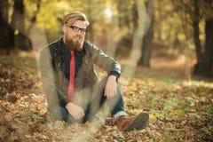 Junger zufälliger Modemann, der im Park sitzt Lizenzfreie Stockbilder