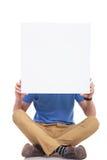 Junger zufälliger Sitzmann mit leerem Brett Stockfoto