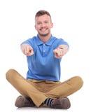 Junger zufälliger Sitzmann zeigt mit beiden Händen Lizenzfreies Stockfoto