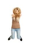 Junger zufälliger Student, der Daumen zeigend springt Stockfoto
