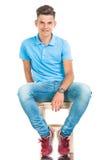 Junger zufälliger Mann, der auf einem Stuhl sitzt Stockfoto
