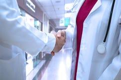 Junges Ärztinabnutzungsstethoskop, das Hände mit medizinischem p rüttelt stockfoto