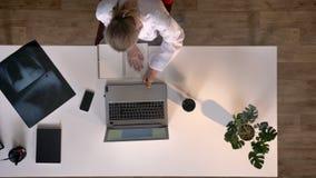 Junges Ärztinschreiben auf Papier und Sitzen bei Tisch mit Laptop und Röntgenstrahlscan, topshot, medizinisches Konzept stock video footage