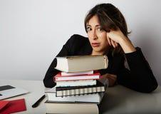 Junges überwältigtes Mädchen, das stark studiert Müde, betonte und überbelastete junge Studentin Weibliches Modell zwischen einem Stockfotografie