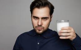 Junges überzeugtes Mannholding-Handglas frische Milch auf grauem Hintergrund stockbilder