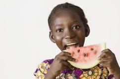 Junges afrikanisches Mädchen, das etwas Wassermelone, lokalisiert auf Weiß isst lizenzfreies stockbild