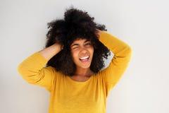 Junges afrikanisches Mädchen, das gegen weißen Hintergrund lacht und blinzelt Stockfoto