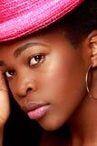 Junges Afroamerikaner-Mädchen mit einem rosa Hut Lizenzfreie Stockfotos
