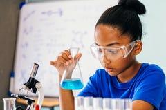 Junges Afroamerikanerkind, das Chemieexperiment tut lizenzfreie stockfotos
