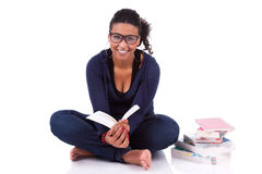 Junges Afroamerikanerkursteilnehmermädchen, das ein Buch liest Stockfotografie