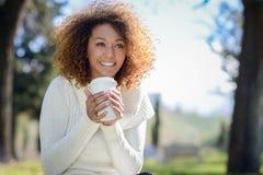 Junges Afroamerikanermädchen mit Afrofrisur mit Kaffeetasse lizenzfreies stockfoto