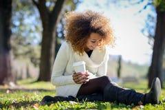 Junges Afroamerikanermädchen mit Afrofrisur mit Kaffeetasse lizenzfreie stockbilder