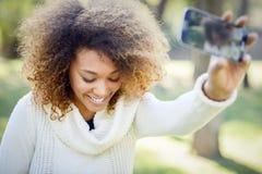 Junges Afroamerikanermädchen selfie im Park mit einem Smartphone lizenzfreies stockbild