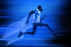 Junges Afroamerikanermannlaufen lokalisiert auf blauem Studiohintergrund stockfotografie