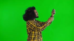 Junges Afroamerikanermannvideo, das mit Telefon auf grünem Schirm oder Farbenreinheitsschlüsselhintergrund nennt Konzept von Gef? stock video