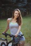 Junges aktives Mädchen mit Fahrrad im Park Lizenzfreie Stockfotos