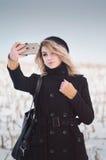 Junges alternatives Mädchen, das selfie auf dem schneebedeckten Gebiet nimmt Lizenzfreie Stockfotos