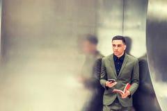 Junges amerikanisches Geschäftsmannlesebuch, simsend am Handy Stockfotografie
