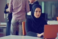 Junges arabisches Geschäftsfrau tragendes hijab, arbeitend in ihrem Startbüro Verschiedenartigkeit, gemischtrassiges Konzept lizenzfreie stockfotografie
