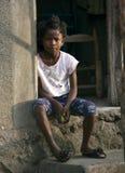 Junges armes haitianisches Mädchen sitzt außerhalb ihres Dorfs, das in ländlichem Haiti geblieben wird lizenzfreies stockfoto