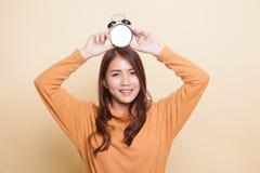 Junges Asiatinlächeln mit einer Uhr lizenzfreie stockfotos