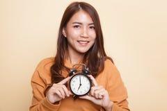 Junges Asiatinlächeln mit einer Uhr lizenzfreie stockbilder