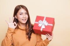 Junges Asiatinshow O.K. mit einer Geschenkbox stockfotos