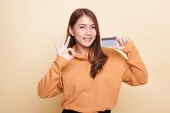 Junges Asiatinshow O.K. mit einer leeren Karte stockbild
