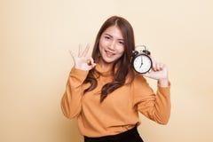Junges Asiatinshow O.K. mit einer Uhr stockfoto