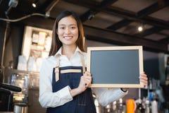 Junges asiatisches Frauen barista, das leeres Tafelmenü in der Kaffeestube hält stockfotos