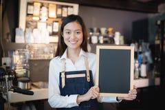 Junges asiatisches Frauen barista, das leeres Tafelmenü in der Kaffeestube hält lizenzfreie stockfotos
