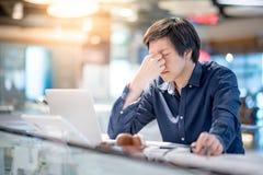 Junges asiatisches Geschäftsmanngefühl beim Arbeiten betont mit Schoss stockbilder
