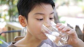 Junges asiatisches Kind, das ein Glas Wasser trinkt stock footage