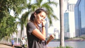 Junges asiatisches Läufer-Mädchen setzt Kopfhörer an und dreht Musik am intelligenten Mobiltelefon im Stadt-Park 4K, Slowmotion stock video