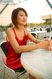 Junges asiatisches Mädchen, das auf im Freienkaffee wartet Lizenzfreies Stockfoto