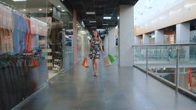 Junges asiatisches Mädchen, das in Einkaufszentrum mit Einkaufstaschen geht stock video