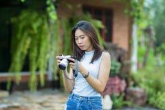 Junges asiatisches Mädchen, das Foto auf Kamera überprüft Lizenzfreie Stockfotografie