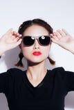 Junges asiatisches Mädchen, das Gefühl tut Angekleidet in einem schwarzen Hemd und ein gelber Rock, Gläser und hellen Lippen, mod stockfotografie