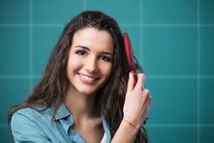 Junges asiatisches Mädchen, das Haar mit dem Finger getrennt auf weißem Hintergrund kämmt Lizenzfreie Stockfotografie