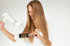 Junges asiatisches Mädchen, das Haar mit dem Finger getrennt auf weißem Hintergrund kämmt Frau, die schönes langes Haar unter Ver Lizenzfreies Stockbild