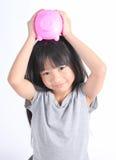 Junges asiatisches Mädchen, das Sparschwein hält Lizenzfreies Stockfoto