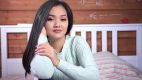 Junges asiatisches Mädchen der netten Weichheit, welches die Kamera sitzt auf Bett im Schlafzimmer aufwirft und betrachtet stock footage