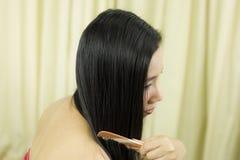 Junges asiatisches M?dchen, das Haar mit dem Finger getrennt auf wei?em Hintergrund k?mmt Nahaufnahme von Sch?nheit Hairbrushing- stockfoto