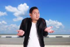 Junges asiatisches Mann-Achselzucken-Don-` t kennen Geste Stockbilder