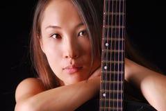 Junges asiatisches Modell, das zur Kamera mit Gitarre schaut Lizenzfreie Stockfotografie