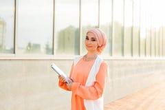 Junges asiatisches moslemisches Geschäftsfraulächeln und -holdingdateidokument lizenzfreie stockfotos