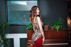 Junges asiatisches sexuelles Modell, das nahe einem Klavier im eleganten Kleid aufwirft Lizenzfreie Stockfotografie
