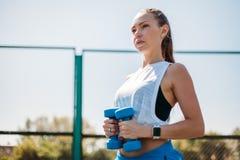 Junges athletisches Mädchen, das Übungen mit Dummköpfen tut Aufstellung auf Sportfeld Porträt Nette glückliche und überzeugte Eig lizenzfreie stockfotos