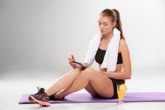 Junges athletisches Mädchen, das mit Laptop herein sitzt Stockbilder